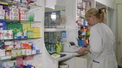 Pharmacist assistant selling medicines at pharmacy checkout counter - stock footage