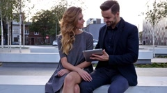 Young couple  sitting on a bench. Man is holding tablet pc. Positive emotions Stock Footage