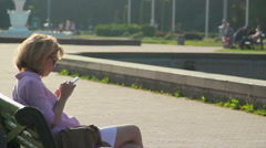 Young female sitting in park, chatting on smartphone, reading news on gadget - stock footage