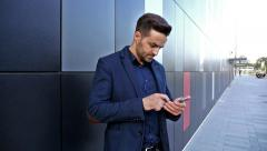 Businessman standing outside office building and using smartphone. Outdoor photo Stock Footage