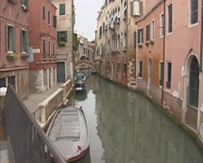 Facades of row houses alongside a venetian canal  + pan around the corner Stock Footage