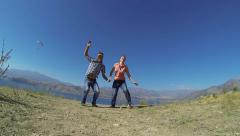 Stock Video Footage of Couple of tourists jumping near Charvak lake in Uzbekistan