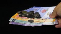 Malaysia Ringgit banknotes and coins fall on black background. Slow Motion. 720p Stock Footage