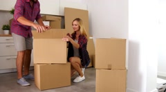 Young couple just move to their new apartment. They are unpacking stuff. - stock footage