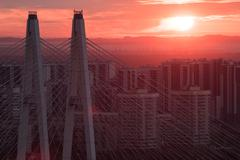 Pylons cable-stayed bridge against the backdrop of urban residential district Stock Photos