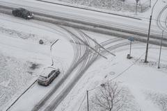 Snowy winter in the city, cloudy day, two cars at the intersection Stock Photos