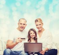 happy family with laptop computer and credit card - stock photo