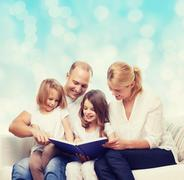 Happy family with book at home Stock Photos