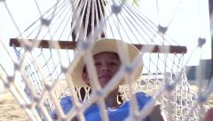 Asian woman, girl relax on a hammock on the sunny beach with coconut trees - stock footage