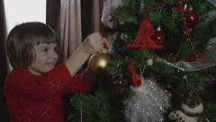 Young beautiful girl decorating the Christmas tree - stock footage
