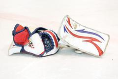 Goalkeeper gloves discarded on the ice - stock photo