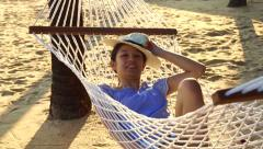 Girl wearing hat relax on a hammock on the sunny beach with coconut trees Stock Footage