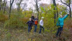 Four happy children in the autumn forest with the teacher exploring nature. - stock footage
