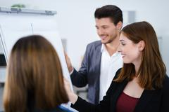 Three businesspeople standing together working at whiteboard Stock Photos