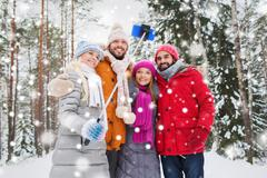 smiling friends with smartphone in winter forest - stock photo