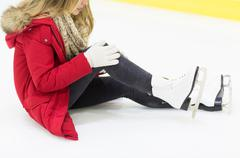 Young woman with knee trauma on skating rink Stock Photos
