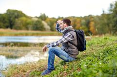 Smiling man with backpack resting on river bank Stock Photos