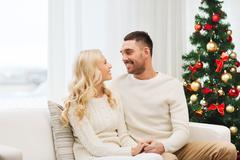 Stock Photo of happy couple at home with christmas tree