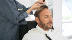 Middle-aged man having a haircut at hairdressing salon - stock footage