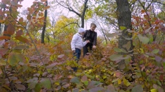 Mom and daughter in the park considering yellowed leaves. - stock footage