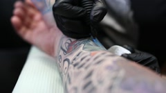 Getting a tattoo forearm by tattoo artist Stock Footage