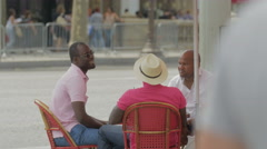 Three men sitting at a table at Le Madrigal restaurant, Paris Stock Footage