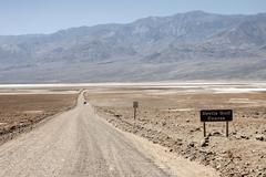 Gravel road to Devils Golf Course Panamint Range behind Black Mountains Death Stock Photos