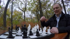 Man with young men playing chess in a park in autumn. Close-up. - stock footage