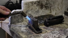 Human warms up the mold for casting billets of metal, the front part Stock Footage