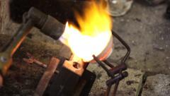 The heating a small crucible with liquid silver and pouring into a mold Stock Footage