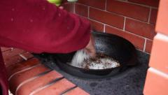 Human hand added white rice in the boiling oil with meat and mixing it Stock Footage