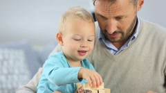 Daddy with 2-year-old boy playing with wooden blocks Stock Footage