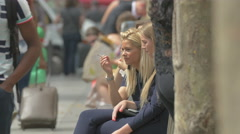 Two women smoking and sitting on a bench on Avenue des Champs-Elysees, Paris Stock Footage