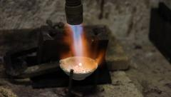 The torch heats a small crucible with pieces of silver,  workshop jewelry Stock Footage