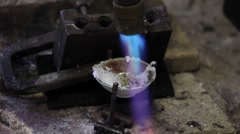 burner heats a small crucible with mixture of the flux with particles of silver - stock footage
