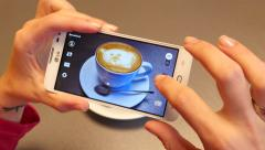 Girl take a photo via smart phone of cappuccino in bar for social web instagram Stock Footage