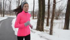 Asian woman running in winter gloves and headband - stock footage