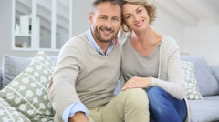 Mature couple relaxing in couch at home - stock footage