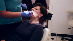 Stock Video Footage of Dentist curing a female patient, clinic, procedure, dental office, sterile utens