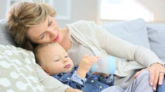 Mother cuddling her baby boy in sofa - stock footage