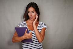 Young woman with straight hair looking surprised while holding tablet - stock photo