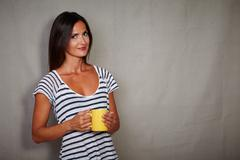 Good-looking brunette female in blue blouse holding coffee cup - copy space - stock photo
