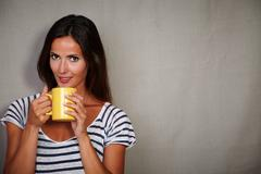 Charismatic lady holding coffee cup while standing against grey texture backg - stock photo