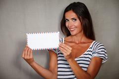 Waist up portrait of a happy woman holding mail while looking at camera - stock photo