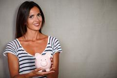 Happy youngster in blue blouse smiling while holding a piggy bank - copy spac - stock photo