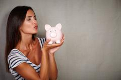 Charismatic young woman in her 30s kissing a piggy bank with eyes closed - stock photo