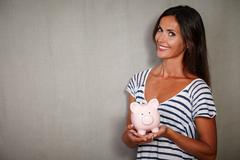 Charismatic lady in casual clothing holding moneybox while smiling - copy spa - stock photo