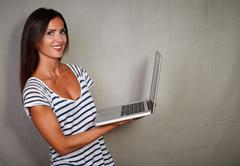 Happy brunette lady holding wireless laptop while looking at camera - stock photo
