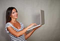 Young woman in her 30s using laptop while looking at camera - grey texture ba - stock photo
