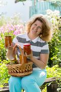 Housewife with a homemade preserves in  garden - stock photo